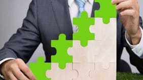 a man in a business suit placing green and white puzzle pieces