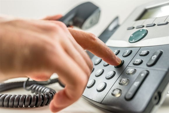 hand dialing a corded phone